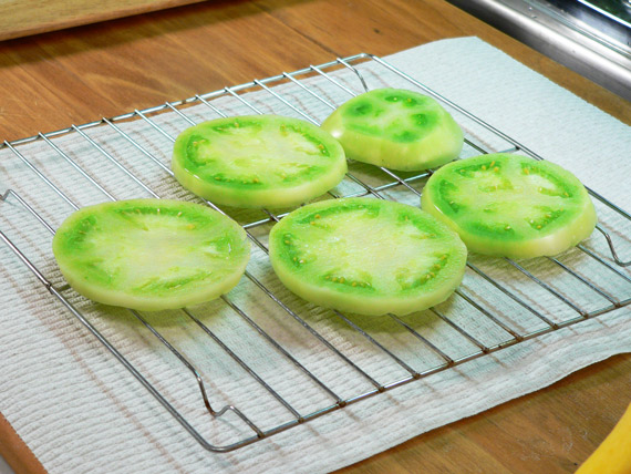Sliced green tomatoes on a wire rack.