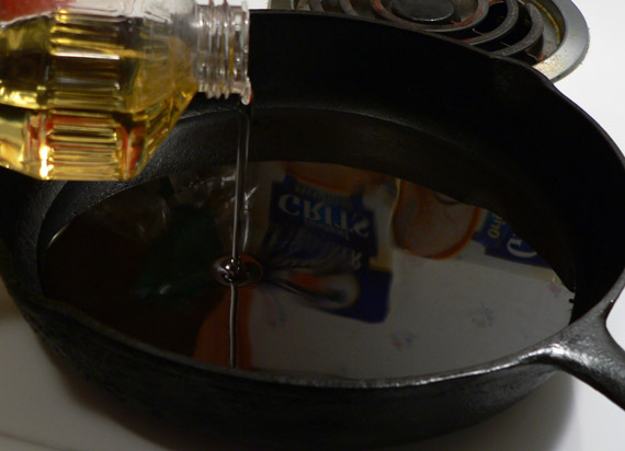 Adding oil to the cast iron skillet.
