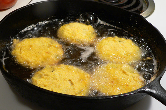 Green tomato slices frying in the cast iron skillet.