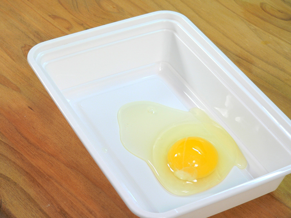 Break an egg into a shallow dish.