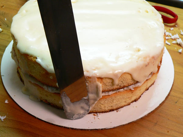 Baker's Coconut Cake, place icing on the second layer and on the sides.