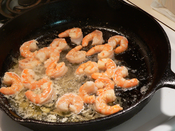 Seafood Mac and Cheese, stir and flip the shrimp until lightly cooked.