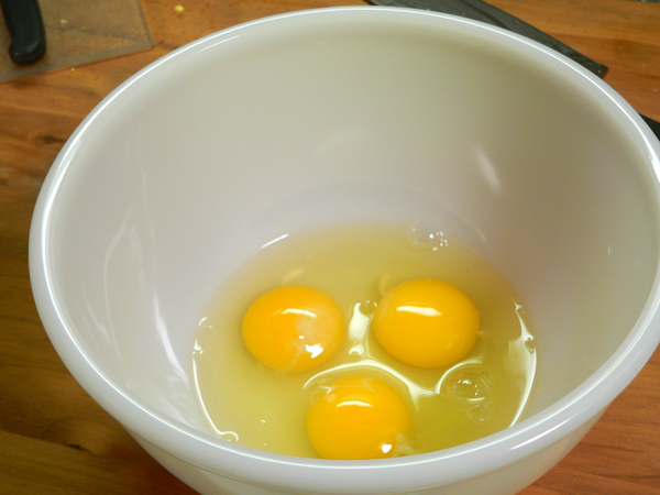 Corn Pudding, crack the eggs.