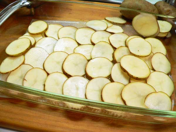 Hamburger Casserole, layer potatoes in the dish.