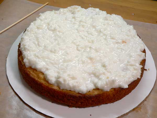 Sour Cream Coconut Cake, add frosting to the top of the first layer.