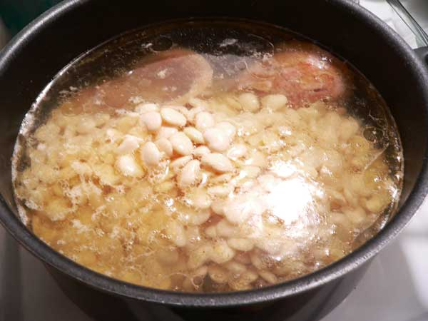 Lima Beans with Ham Hocks and Rice, add the Lima beans to the pot of water.