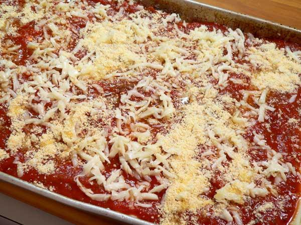 Lasagna, add sauce and cheese.