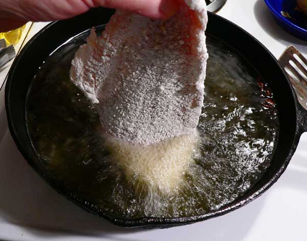 Fried Catfish, place fish in oil.