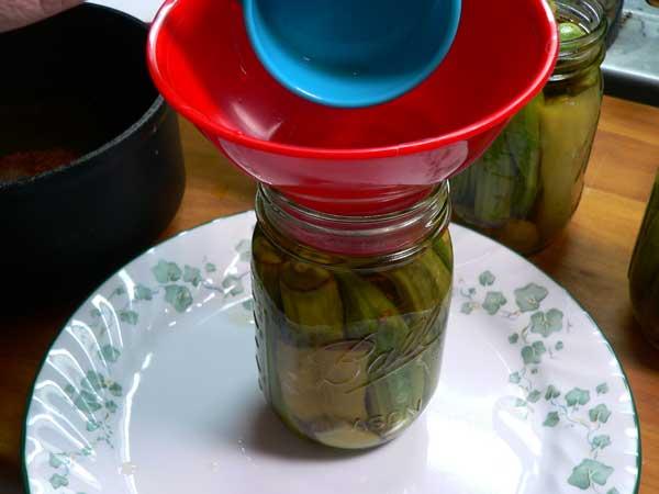 Pickled Okra, add the brine to the jar.